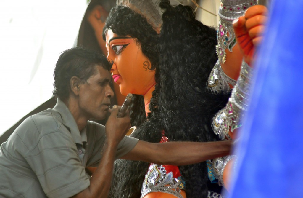 Artist gives finishing touch to idol of Goddess Durga at the Kumartoli workshop for upcoming Durga puja festival in Kolkata on Oct.4, 2013. (Photo: IANS)