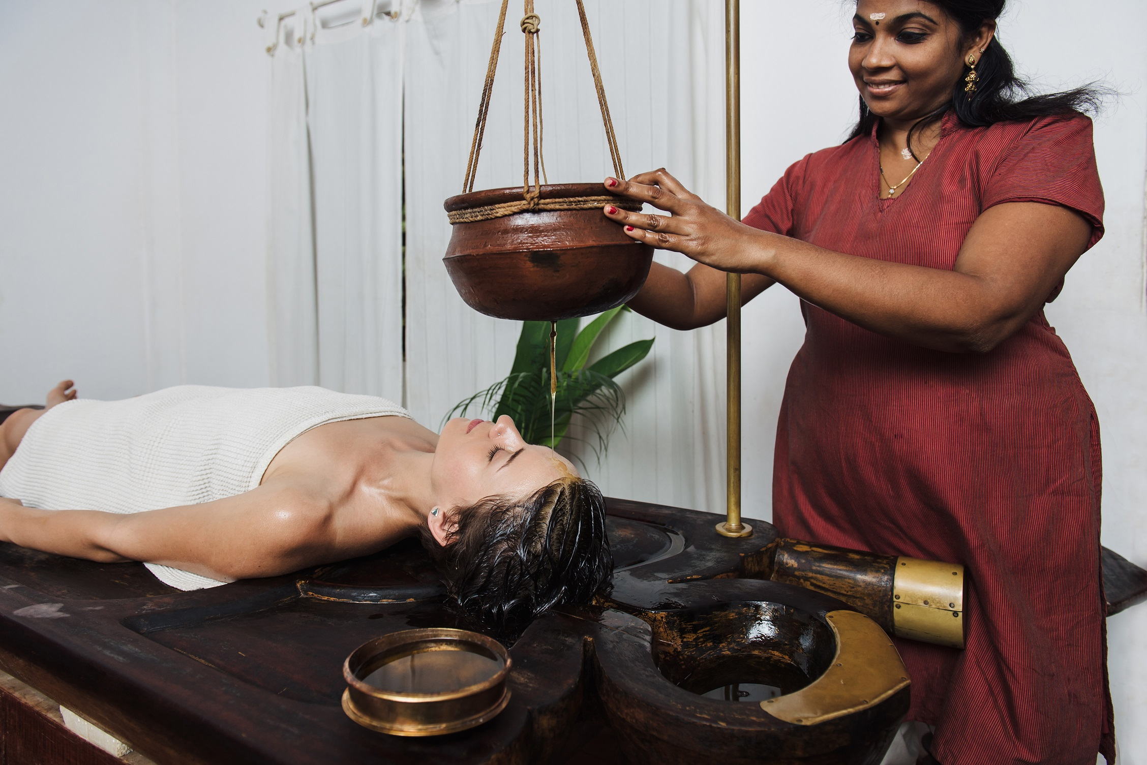 Caucasian woman having Ayurveda shirodhara treatment in India, Kerala state