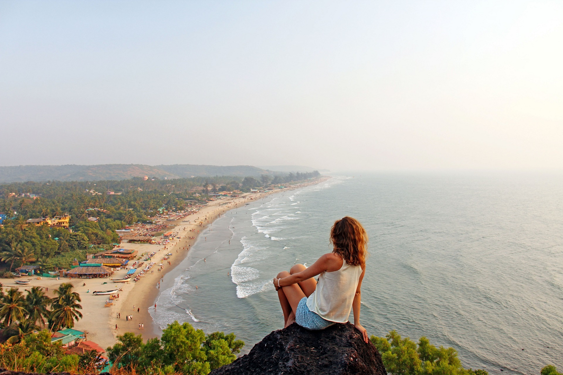A young girl with blond hair sits on top of a mountain and looks at the sea and beach of the village of Arambol, Goa, India. The beach from a height. Relax and relax alone with nature